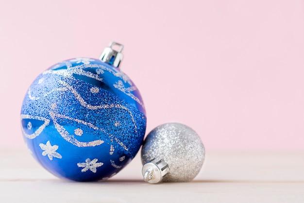Два рождественских украшения на розовом фоне