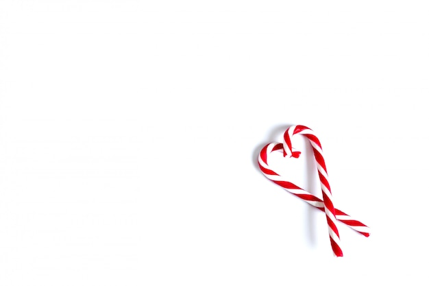 Two christmas red and white candies, christmas candy canes folded in the shape of a heart on a white background