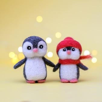 Bokeh와 노란색 배경에 두 크리스마스 장난감 felted 양모 귀여운 작은 펭귄