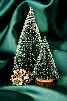 녹색 실크 배경에 두 개의 크리스마스 트리입니다. 트렌디한 장식. 크리스마스 휴일 축 하입니다. 새 해 개념입니다. 인사말 카드. 전나무 나무와 크리스마스 배경입니다. 복사 공간