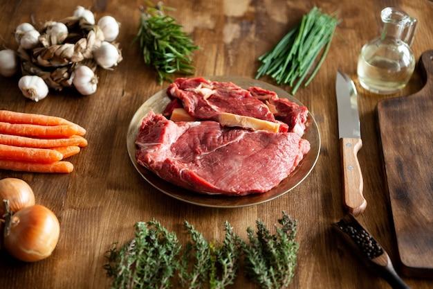 素朴な木製のテーブルの上に新鮮な野菜を中心とした赤身の肉の2つの塊。美味しい野菜。シェフナイフ。