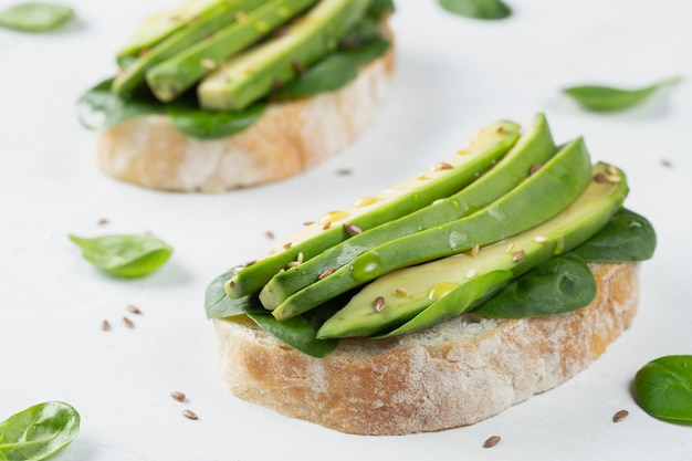 Two ciabatta toast with sliced avocado olive oil