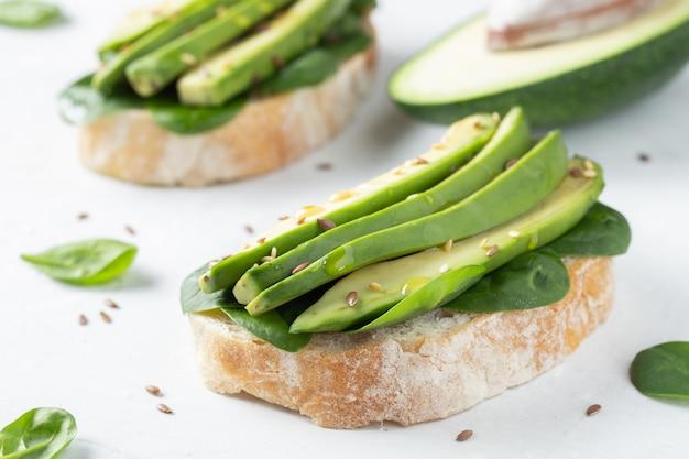 Two ciabatta toast with sliced avocado.