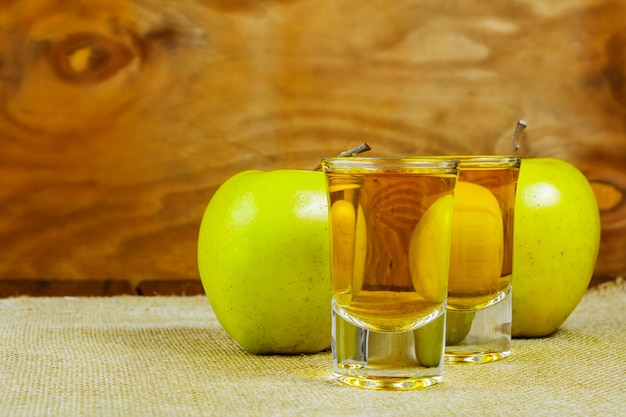 Two cider glasses and green apples