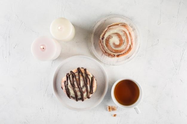 Две булочки cinnabon на светлом фоне с чашкой чая. вид сверху с копией пространства.