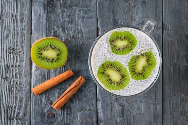 Two cinnamon sticks, chia seed pudding with kiwi fruit on a dark wooden table. the view from the top. flat lay.