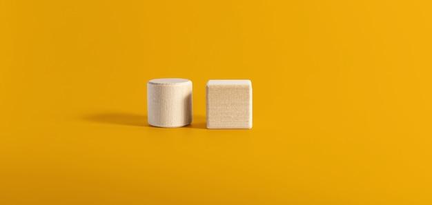 2つの円形と正方形の木製ブロックが黄色の背景に並んで配置されています。ウッドブロックのコンセプト、テキスト、ポスター、モックアップテンプレートのコピースペースのバナー。