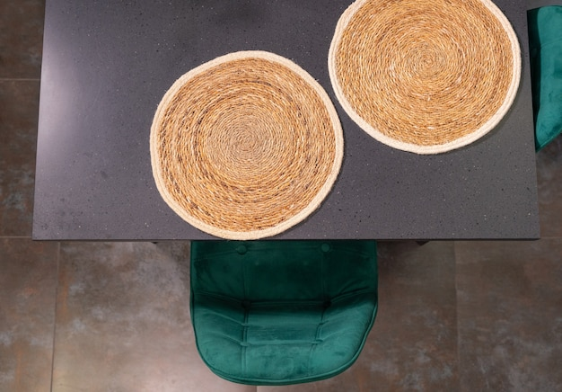 Two circular woven straw placemats on a kitchen table
