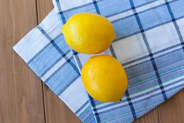 キッチンタオルの上の木製のテーブルに2つの柑橘類のレモン
