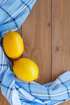 Два цитрусовых лимона на деревянном столе с кухонным полотенцем