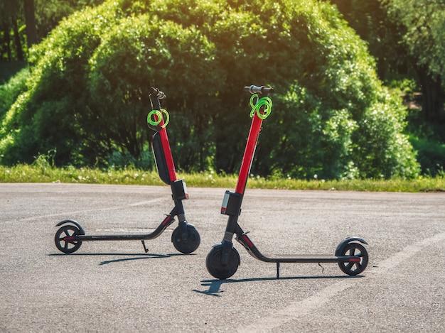 アスファルト上の2つの都市スクーター。夏の街に駐車した2台のスクーター。現代の若者の移動手段
