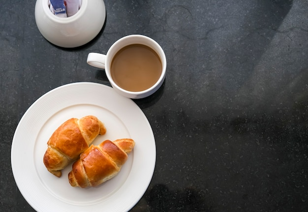 Two classic croissants on the white plate and cup of coffee on dark slate table. top view. morning routine and breakfast concept. dark background.