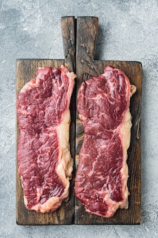 Two classic fresh beef steaks, on gray table, top view flat lay