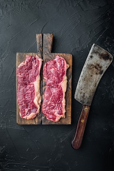 Два классических свежих стейка из говядины на черном фоне, плоская планировка, вид сверху