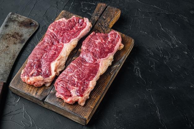 Два классических стейка из свежей говядины на черном фоне