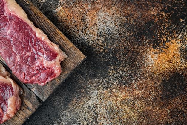 Два классических свежих стейка из говядины на старом темном деревенском фоне, плоская планировка, вид сверху
