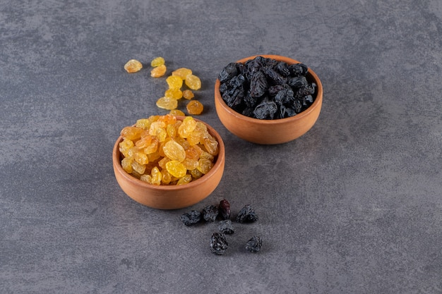 Two clay bowls with black and golden raisins on stone background.