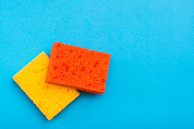 青色の背景に皿を洗うための2つのきれいな新しい色のスポンジ。掃除機のコンセプト。