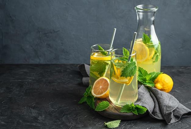 Два прозрачных стакана и графин освежающего, полезного лимонада на темном фоне. вид сбоку, копия пространства.