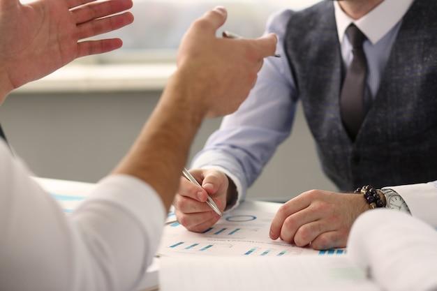 Two clerk businessmen deliberating on problem at desk
