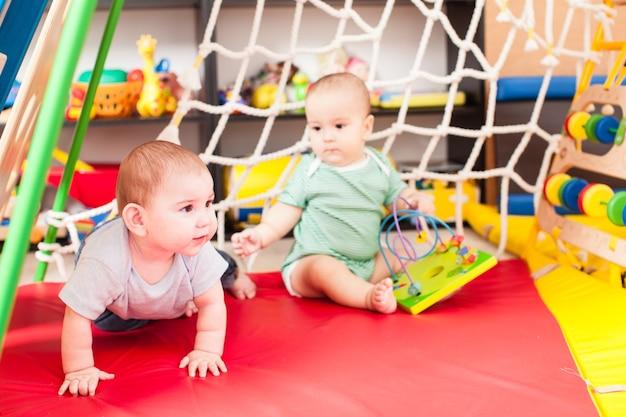 Двое умных мальчиков-младенцев играют с игрушкой в игровой комнате