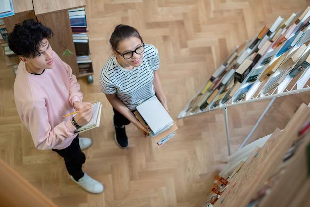 Два умных студента-подростка в повседневной одежде смотрят на одну из книжных полок в библиотеке колледжа во время подготовки к семинару