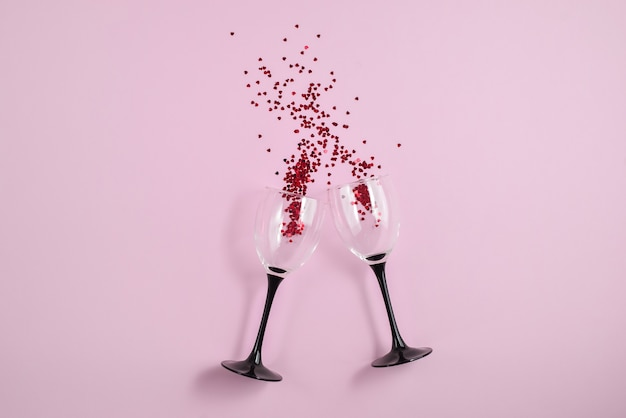 Two clinking wine glasses poured out red heart confetti on pink color paper background.