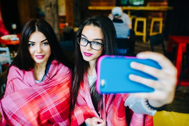 Two close girlfriends want to make a selfie in the cafe on memory