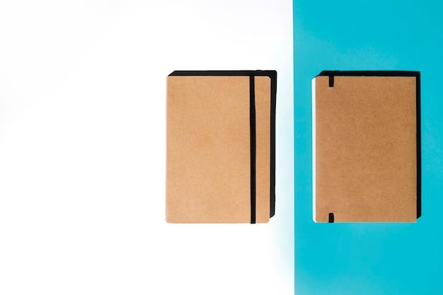 白と青の背景に茶色のカバー付きの2つの閉じたノートブック