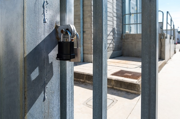 Два закрытых навесных замка на металлической входной двери на электростанцию металлический замок