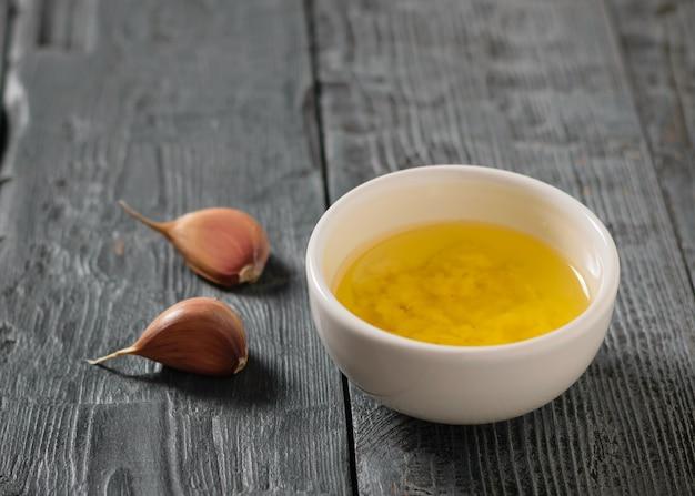 Два зубчика чеснока и миску с оливковым маслом и чесноком на темном столе. заправка для диетического салата.
