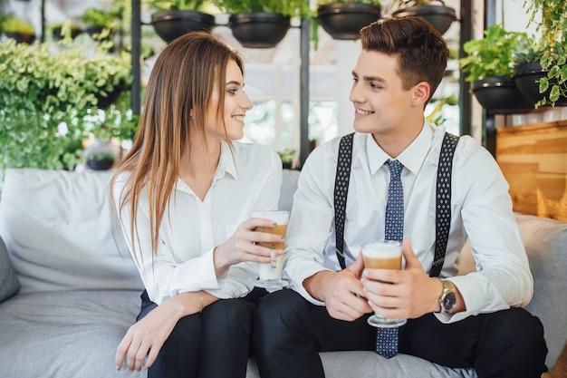 Два сотрудника общаются во время перерыва в умном пространстве. одет в белые рубашки. латте в руках.