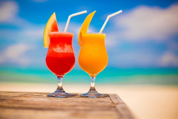 Two cocktails fresh watermelon and mango of stunning turquoise sea