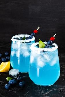 Два коктейля со льдом, блю кюрасао и черникой
