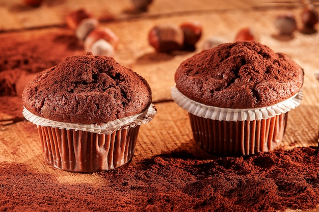Two cocoa muffins and cocoa powder on a wooden board
