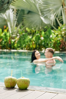 Two coconut cocktails on edge of swimming pool, couple dancing and hugging in water