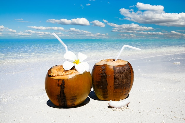 Two coconut cocktails on white sand beach next to clean sea water. vacation and travel concept