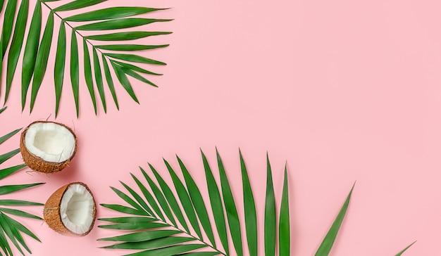 분홍색 배경에 야자수가 있는 두 개의 코코넛 반쪽. 상위 뷰, 복사 공간입니다.