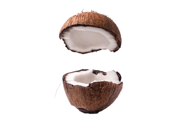Two coconut section halves isolated on white background one broken in two brown fibrous shell with milk meat