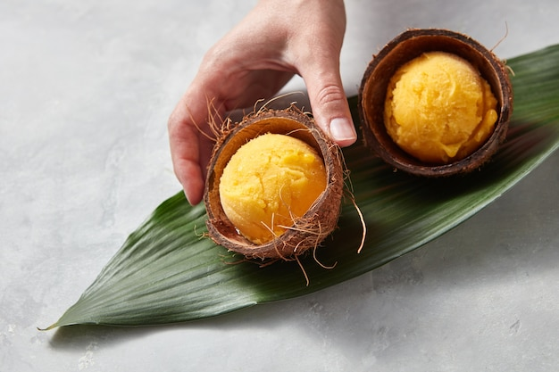 Two coconut shells with balls of apetitic mango ice cream on a green leaf on a gray concrete table with copy space for text. girl's hand takes ice cream. top view