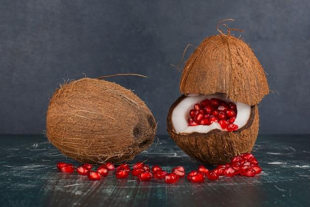 大理石の表面にザクロが付いた2つのココナッツ