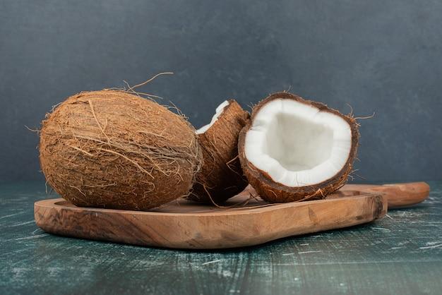 Due noci di cocco sulla tavola di legno sulla superficie di marmo