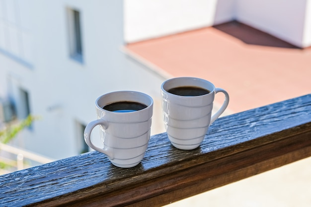 Two coffee cup  in wooden balcony terrace.