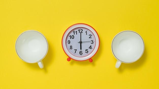 黄色の背景に2つのコーヒーカップと赤い目覚まし時計。朝のトーンを持ち上げるというコンセプト。