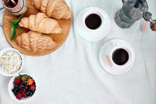 Две кофейные чашки и итальянская кофеварка с круассаном и фруктами над столом в домашней утренней концепции ритуалов завтрака, фоне еды образа жизни.