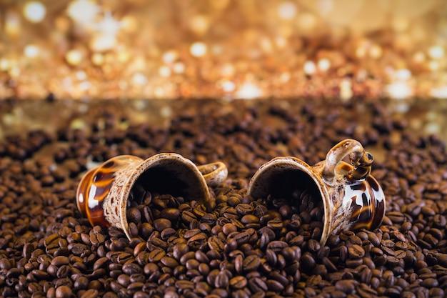 볶은 커피 콩으로 가득 찬 두 개의 커피 컵. 아름 다운 커피 배경입니다.