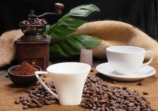 Two coffee cups,ground coffee ,roasted coffee beans,grinder, and monstera leave on wooden table with burlap  background