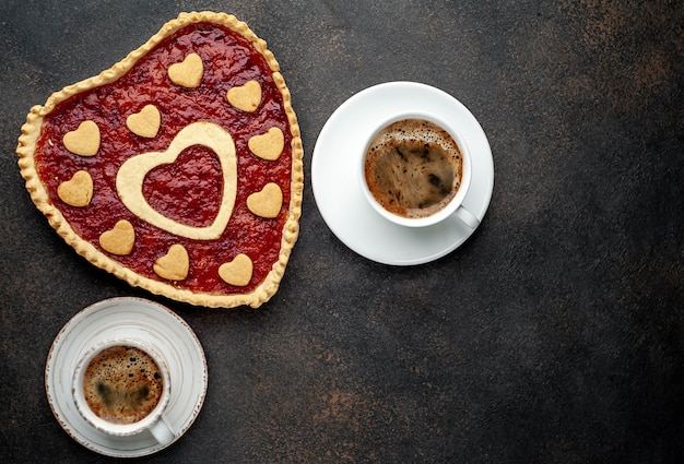 Two coffee cups and heart-shaped cake for valentine's day
