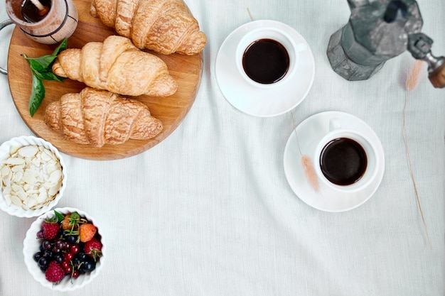 Two coffee cups and italian coffee maker with croissant and fruits over table at home morning breakfast rituals concept, lifestyle food background.