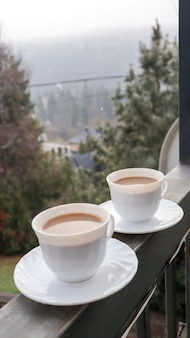 아침에 산 풍경이 있는 발코니에 두 개의 커피 컵. 가을 숲의 마법 같은 전망과 함께 발코니 옆에 서서 모닝 커피 두 잔.